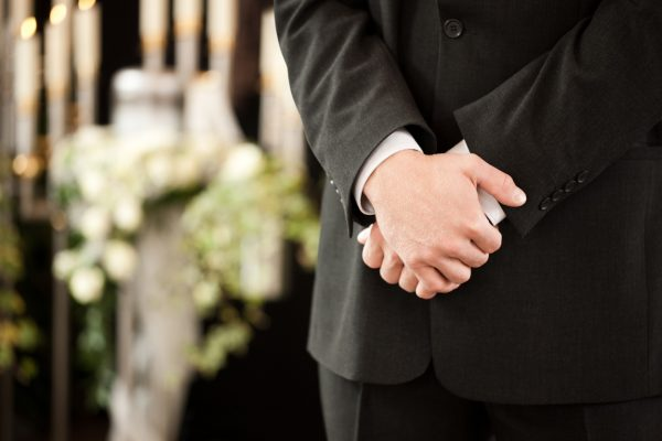 Religion, death and dolor  - undertaker at funeral standing in front or urn